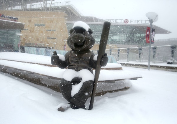 A statue of TC Bear, the Minnesota Twins mascot, is coated in fresh snow on April 3. Another bout of heavy snow is expected this weekend.