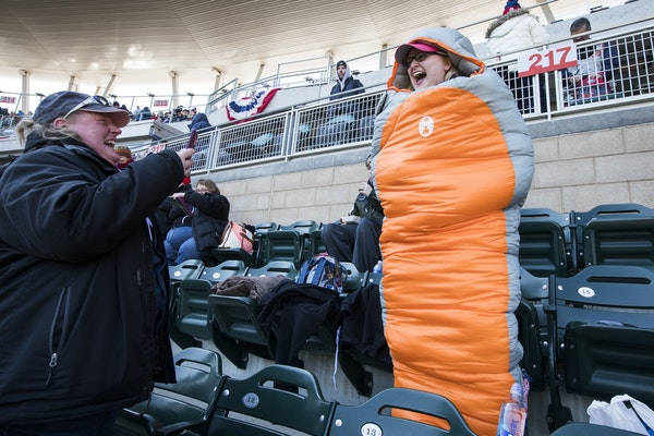 Brittany Workman, right, laughs as she poses for a photo by Beverly Warmka, both of Minneapolis, while wearing a sleeping bag she brought to stay warm