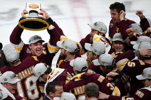 Minnesota Duluth forward Karson Kuhlman hoisted the NCAA championship trophy over his head while celebrating with teammates following a 2-1 victory ov