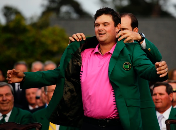 Former Masters champion Sergio Garcia helps Patrick Reed with his green jacket after winning the Masters