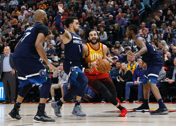 Utah Jazz's Ricky Rubio, middle, drives the basket as Minnesota Timberwolves' Tyus Jones (1) defends during the second half of an NBA basketball game