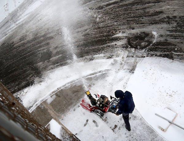 Seen from the 24th Street footbridge, a man blows snow Saturday in Minneapolis.