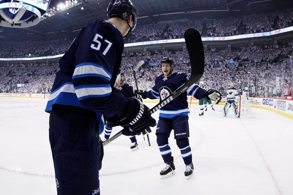 Winnipeg Jets' Tyler Myers (57) and Andrew Copp (9) celebrate Myers' goal against the Wild during the second period of Game 2