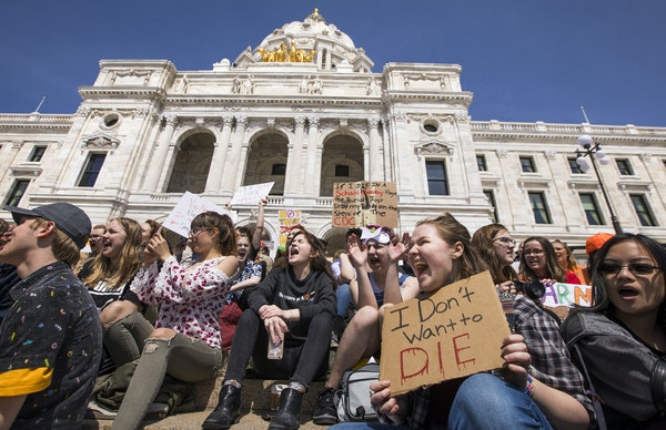"""Cate Barnes, second from right, a junior at Avalon Charter School in St. Paul, chants with a sign that reads """"I don't want to die"""" during a rall"""