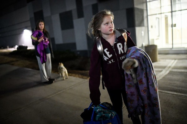 Natalia Johnson, 12, right, and her sister Iley, 15, stood outside Amsoil Arena in Duluth with their 6-year old pug, Tucker, and some of their belongi