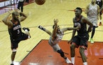 Minnesota Timberwolves' Jeff Teague, center, shoots between Houston Rockets' Chris Paul, left, and Clint Capela during the second half in Game 1 of a