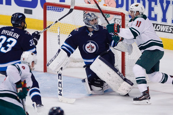 Jets goaltender Connor Hellebuyck looks up at Minnesota Wild's Zach Parise as he saves a shot during the first period of Game 1