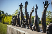"""""""Raise Up,"""" a sculpture by Hank Willis Thomas, on the grounds of the new National Memorial for Peace and Justice in Montgomery, Ala., April 20, 2018."""