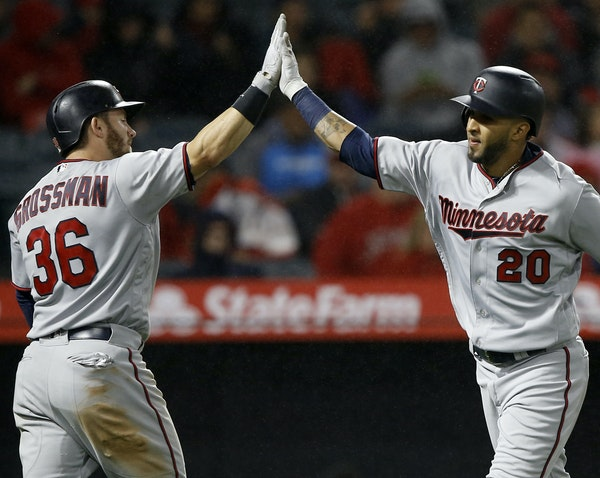 Minnesota Twins' Eddie Rosario, right, gets congratulations from Robbie Grossman after Rosario hits a solo home run against the Los Angeles Angels d