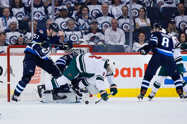 The Jets' Tyler Myers clears the Wild's Charlie Coyle from in front of goaltender Connor Hellebuyck during the second period in Game 5