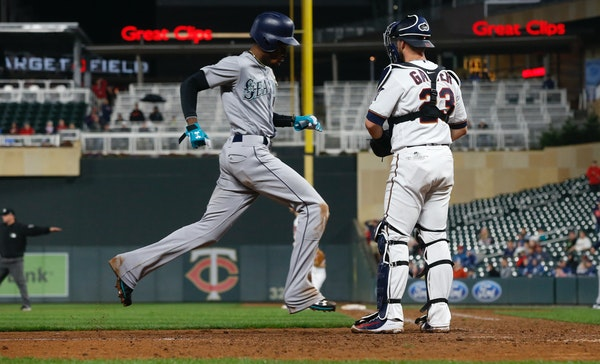 Seattle's Dee Gordon eased his way past Twins catcher Mitch Garver after first baseman Logan Morrison threw a bunt attempt into right field Monday n