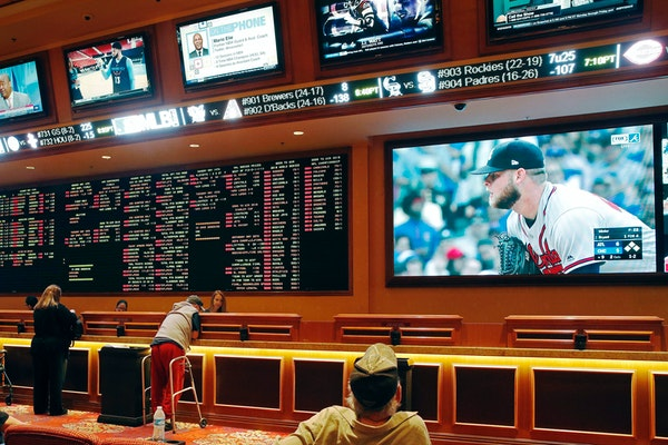 FILE - In this Monday, May 14, 2018 file photo, people make bets in the sports book area of the South Point Hotel and Casino in Las Vegas. Those who d