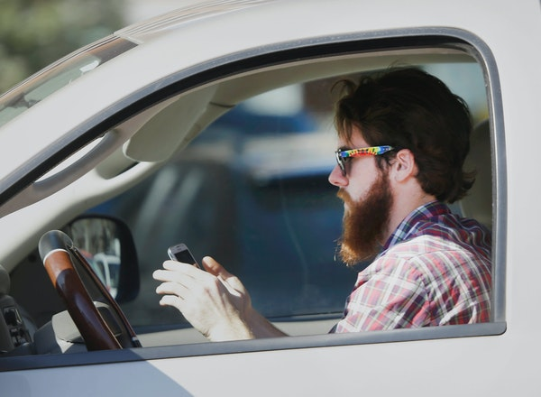 In this Feb. 26, 2013 file photo, a man uses his cell phone as he drives through traffic in Dallas.