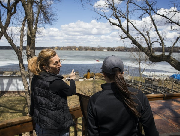 Melissa Hanson, left, shows Meghan Darley, a resource conservation technician with Scott Soil & Water Conservation District, the part of her lakeshore