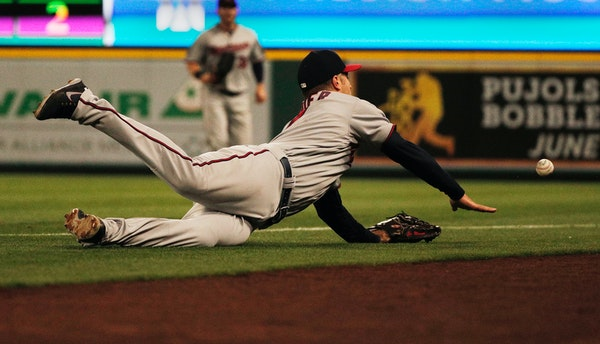 Minnesota Twins first baseman Joe Mauer dives but can't reach a foul ball hit by the Los Angeles Angels' Justin Upton in the third inning at Angel Sta