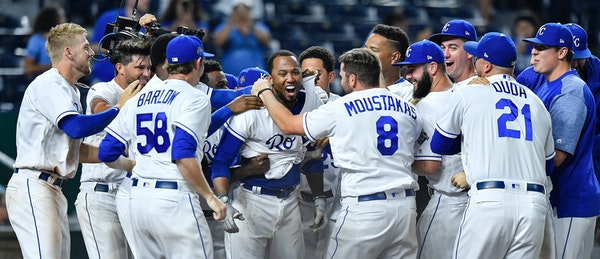 The Kansas City Royals' Alcides Escobar is surrounded by teammates after hitting the game-winning home run in the 14th inning against the Twins