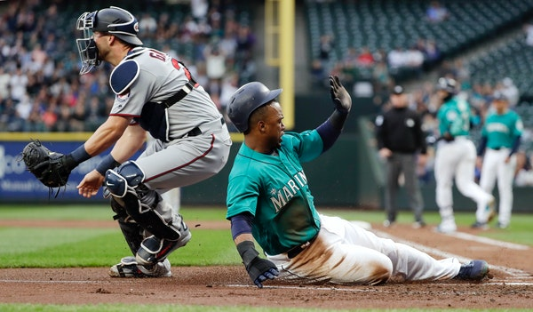 Seattle Mariners' Jean Segura, right, scores as Twins catcher Mitch Garver waits for the throw during the first inning