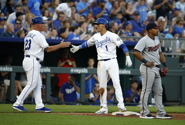 The Royals' Ryan Goins celebrated with third base coach Mike Jirschele after hitting a two-run triple during the second inning against the Twins on