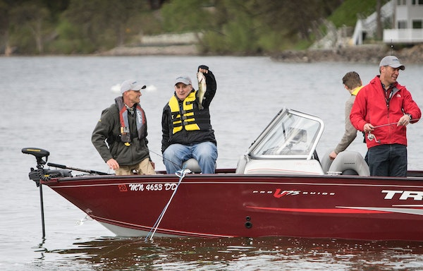Gov Mark Dayton shows off one of the three fish he caught Saturday morning on Green Lake in Spicer, Minn., during the fishing opener on Saturday, May