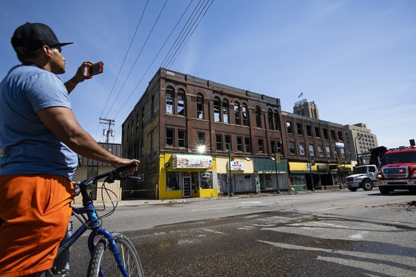 A passerby takes cell phone photos of the aftermath of a three-alarm fire at Lake Street and Chicago Avenue.