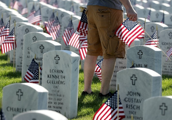 One of several thousand volunteers Saturday planted American flags on each grave at Fort Snelling National Cemetery.