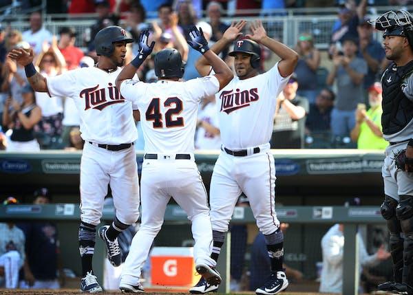 Eduardo Escobar (center) celebrated his eighth inning homer with Eddie Rosario, left, and Gregorio Petit