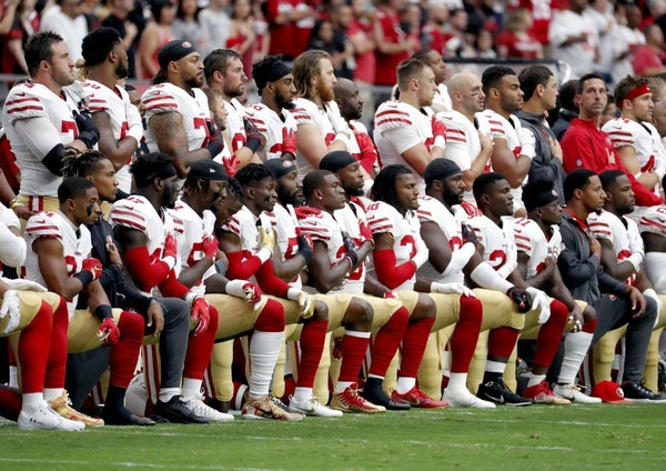 Members of the San Francisco 49ers kneel during the national anthem as others stand during the first half of an NFL football game against the Arizona