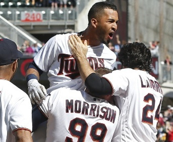 Eddie Rosario celebrated at home plate with his Twins teammates after his walkoff two-run home run off Indians pitcher Cody Allen in the ninth inning