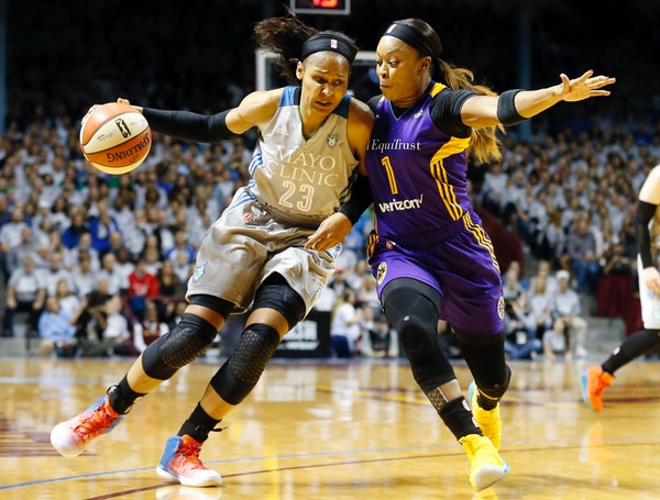 Minnesota Lynx's Maya Moore, left, drives around Los Angeles Sparks' Odyssey Sims during the first half of Game 5 of the WNBA Finals in Minneapolis la