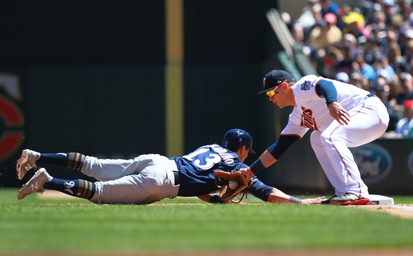 Twins first baseman Logan Morrison tagged out Milwaukee's Tyler Saladino in the third inning Sunday.