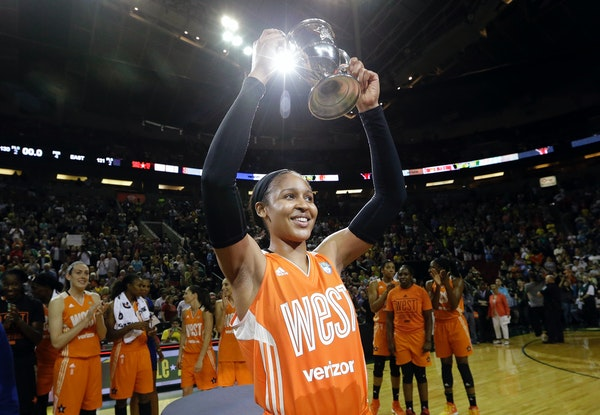 Minnesota Lynx's Maya Moore, of the Western Conference, holds up a trophy after being named most valuable player as teammates cheer behind after the W