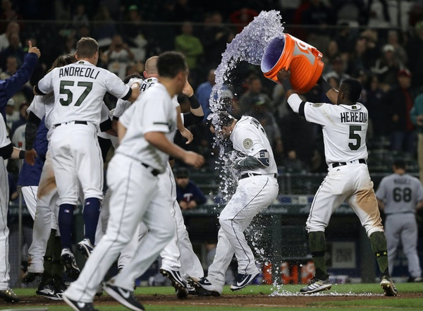 Mariners catcher Mike Zunino was doused with sports drink by teammate Guillermo Heredia, right, after Zunino hit a walkoff home run off the Twins' Mat