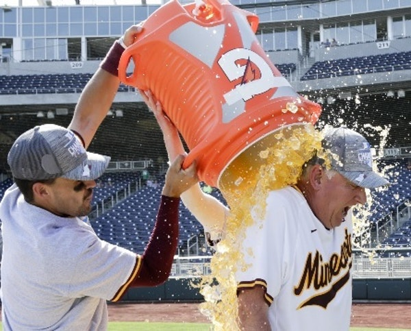 Gophers third baseman Micah Coffey, left, and second baseman Luke Pettersen drenched coach John Anderson following Minnesota's 6-4 victory over Purdue