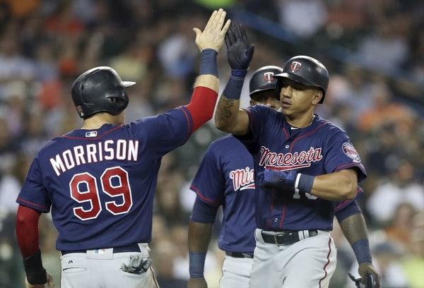 Minnesota Twins' Ehire Adrianza, right, is greeted by Logan Morrison (99) and Miguel Sano, rear, after they scored on Adrianza's grand slam during the