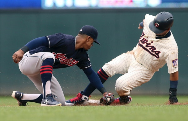 The Twins' Ehire Adrianza beats the tag by Cleveland shortstop Francisco Lindor as he steals second base in the third inning Saturday