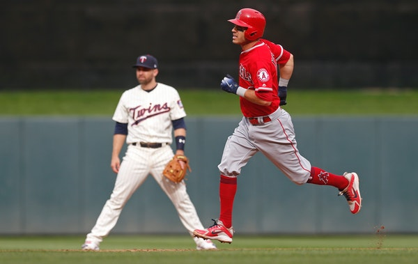 Los Angeles Angels' Ian Kinsler, right, passes by Minnesota Twins second baseman Brian Dozier as he rounds the bases on a solo home run off Twins pitc