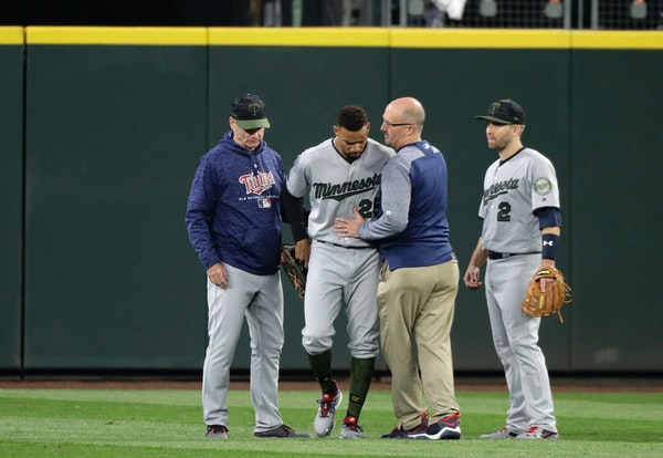 Minnesota Twins center fielder Byron Buxton, second from left, is attended to by head trainer Tony Leo, second from right, after he crashed into the w