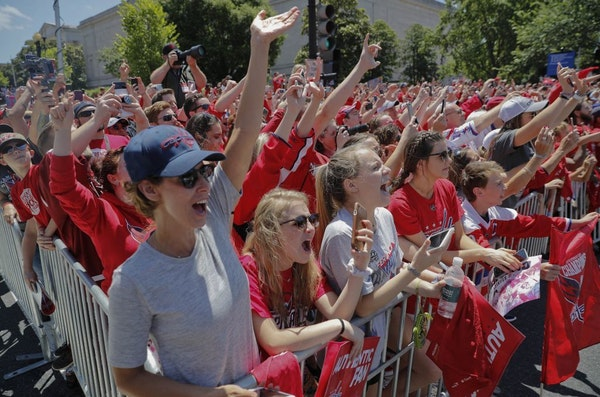 Fan celebrate as they watch the NHL hockey team Washington Capitals Stanley Cup victory parade in Washington, Tuesday, June 12, 2018.