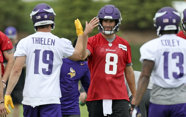 """New Vikings quarterback Kirk Cousins gave receiver Adam Thielen a backhanded-high-five during practice at their new Eagan facility on Wednesday. """"It"""