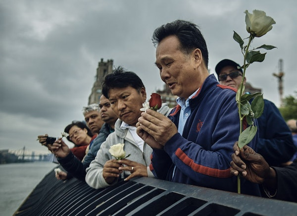 """Richard Chow, right, pays homage to his dead brother Yu Mein """"Kenny"""" Chow, along with friends and other family, at the East River, in New York, Ma"""