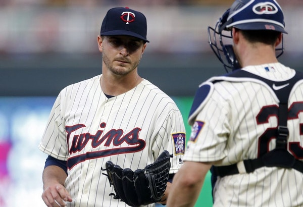Minnesota Twins pitcher Jake Odorizzi, left, gets a visit from catcher Mitch Garver after giving up a walk to Chicago White Sox's Matt Davidson during