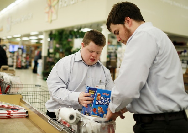 Charlie McGrory bagged groceries at Hy-Vee in Winona with some direction from his job coach, Andy, who happens to be his brother. Charlie carefully ma