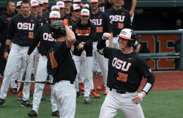 Oregon State's Adley Rutschman (35) celebrates with Micahel Gretler (10) after hitting a solo home run in the first inning of the Corvallis Super Regi