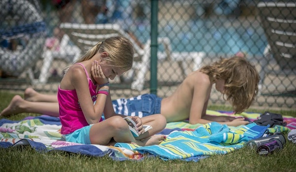 Adam Nafziger's children, Freya, 9, left, and Linus, 11, right, read their books as they waited for the pool to open from a break at the Richfield poo