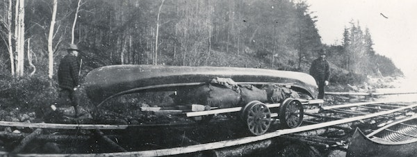 The 139-rod portage between Iron and Crooked lakes, known as Curtain Falls, transports a canoe by rail in 1924.