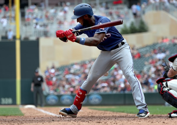 The Texas Rangers' Jurickson Profar is hit by a pitch by Minnesota Twins reliever Addison Reed in the seventh inning, sparking an exchange of words be