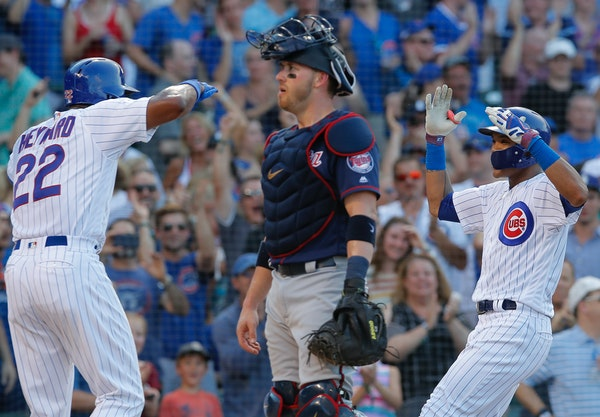 Chicago Cubs' Addison Russell, right, and Jason Heyward, left, celebrate Russell's grand slam, next to Twins catcher Mitch Garver during the fifth inn