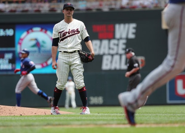 Minnesota Twins starter Jake Odorizzi, middle, watches a run score on a double by the Texas Rangers Shin-Soo Choo, left, during the second inning Satu