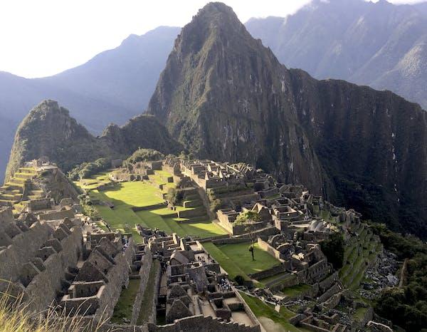 Machu Picchu's citadel near sunset with Huayna Picchu's sharp peak looming behind it.