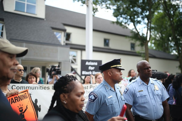 Minneapolis Police Chief Medaria Arradondo, second from right, listened as north Minneapolis community members held a protest and rally outside the Fo